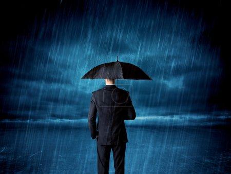 Photo pour Homme d'affaires debout sous la pluie avec un concept de parapluie sur fond - image libre de droit