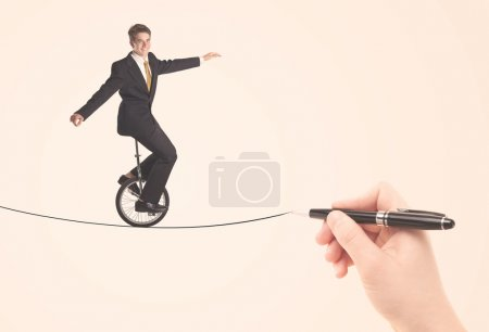 Businessman riding monocycle on a rope drawn by hand
