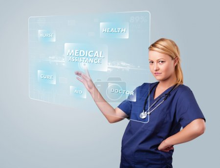 Photo for Young nurse standing and pressing modern medical type of buttons - Royalty Free Image