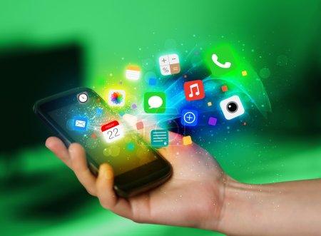 Photo pour Main tenant le smartphone avec concept icônes colorées app - image libre de droit
