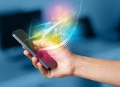 Ruka držící chytrý telefon s abstraktní linie zářící