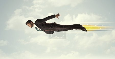 Happy business man flying fast on the sky between clouds