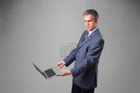 Photo for Handsome businessman in suit holding modern laptop - Royalty Free Image