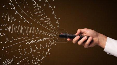 Photo pour Main tenant une télécommande, des lignes bouclées et des flèches sortant de i - image libre de droit