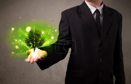 Photo for Young businessman holding a glowing tree in his hand - Royalty Free Image