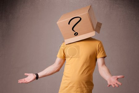 Photo for Young man standing and gesturing with a cardboard box on his head with question mark - Royalty Free Image