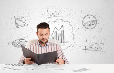 Business man sitting at table with hand drawn graph charts