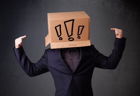 Photo for Young man standing and gesturing with a cardboard box on his head with exclamation point - Royalty Free Image
