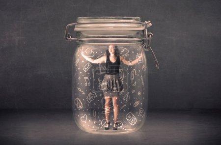 Photo pour Femme d'affaires capturée en pot de verre avec main dessinée concept d'icônes de médias sur fond - image libre de droit