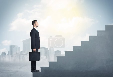 Businessman climbing up a concrete staircase concept