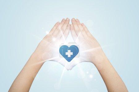 Photo pour Mains créant une forme avec coeur brillant croix bleue au centre - image libre de droit