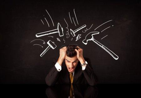Foto de Joven empresario deprimido sentado bajo blanco dibujado golpeando marcas de martillo - Imagen libre de derechos