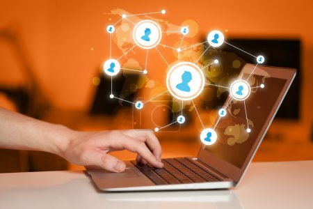 Photo for Close up of hand with laptop and social media network icons - Royalty Free Image