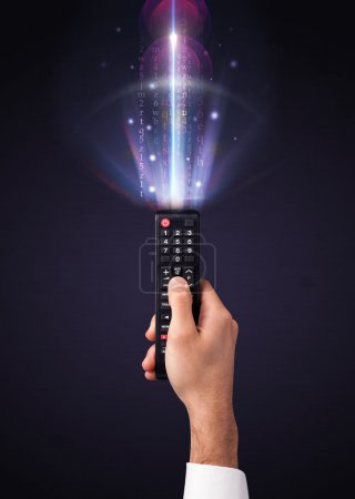 Hand holding a remote control, shining numbers and...