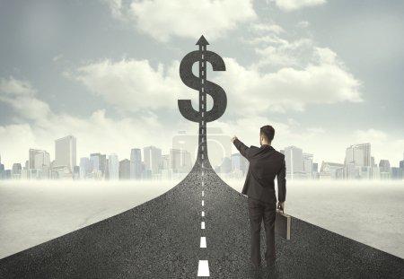 homme d'affaires sur la route menant vers un signe dollar