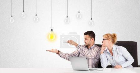Photo pour Homme d'affaires et femme assis à table avec des ampoules lumineuses idée - image libre de droit