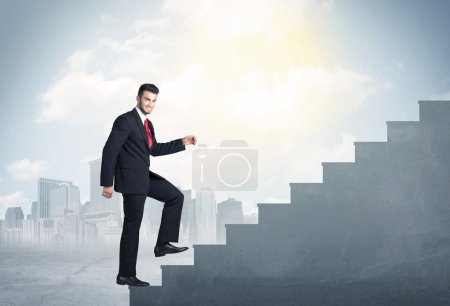 Photo for Businessman climbing up a concrete staircase concept on city background - Royalty Free Image