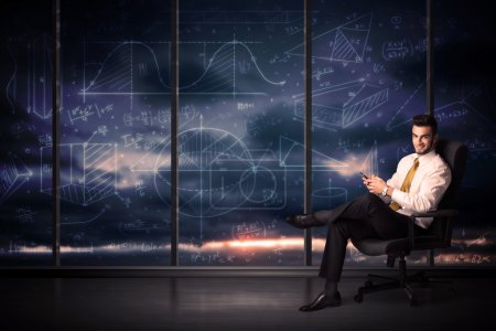 Businessman holding tablet in office room with graph charts on w