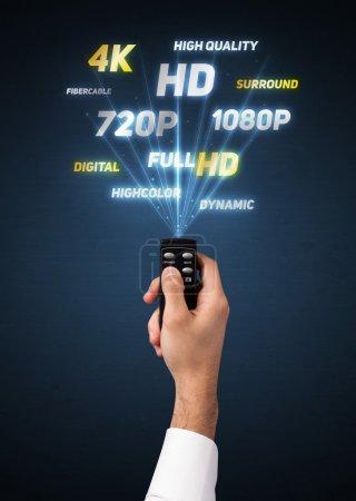 Photo pour Main tenant une télécommande, propriétés multimédia sortant de i - image libre de droit
