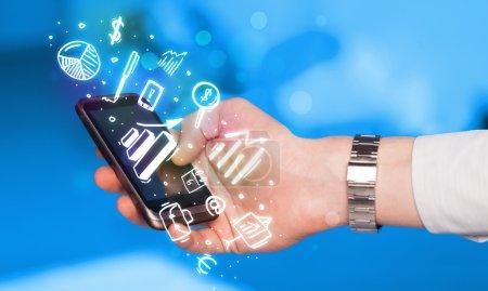Photo pour Smartphone avec la finance et le marché icônes et symboles concept - image libre de droit