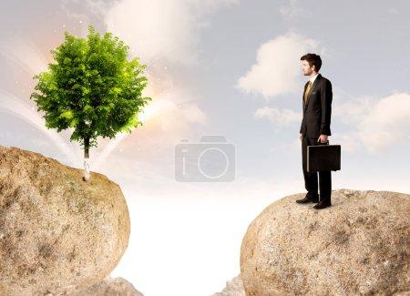 Photo pour Homme d'affaires debout sur le bord de la montagne rocheuse avec un arbre de l'autre côté - image libre de droit