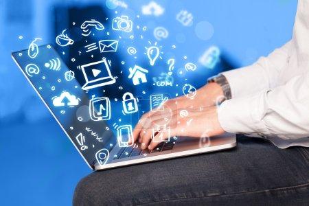 Photo pour Écriture à la main sur ordinateur portable avec icônes médias et symboles sortant - image libre de droit