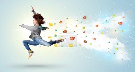 Photo pour Belle femme sautant avec des pierres précieuses colorées et des cristaux sur le concept de fond - image libre de droit