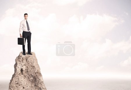 Glücklicher Geschäftsmann steht auf Klippe