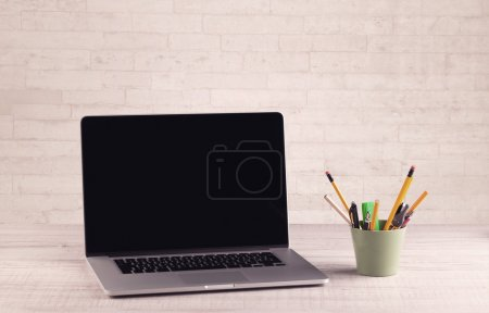 Office desk closeup with white brick wall