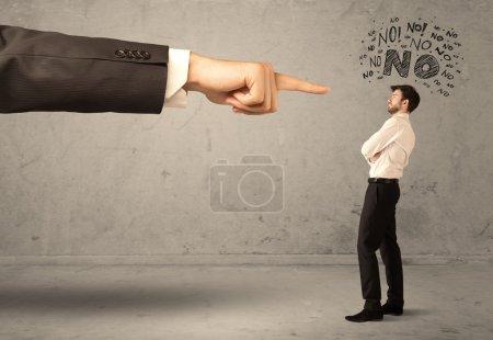 Photo pour Un jeune employé n'est pas d'accord et se dispute avec le patron, se sentant honteux concept. Une grande main pointant vers un homme d'affaires disant non - image libre de droit
