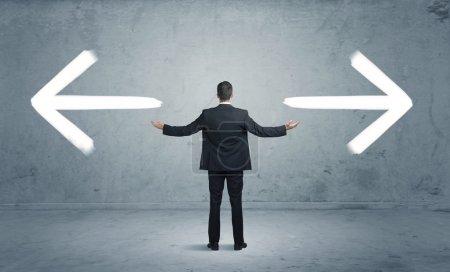 Photo pour Un homme d'affaires dans le doute, devant se départager entre deux choix différents indiqués par des flèches pointant dans la direction opposée concept - image libre de droit
