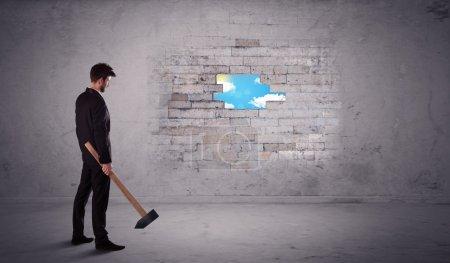 Business man hitting brick wall with hammer
