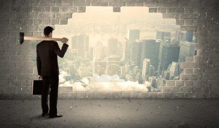 Photo pour Homme d'affaires Cogne le mur avec marteau sur fond de vue ville - image libre de droit