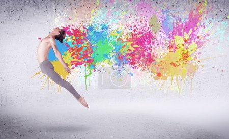 Photo for Modern street dancer jumping with colorful paint splashes on back wall concept - Royalty Free Image