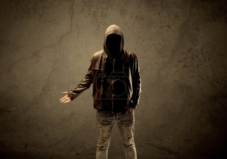 Photo for A suspicious faceless mature male in dark urban environment and light in front of a concrete empty wall background - Royalty Free Image
