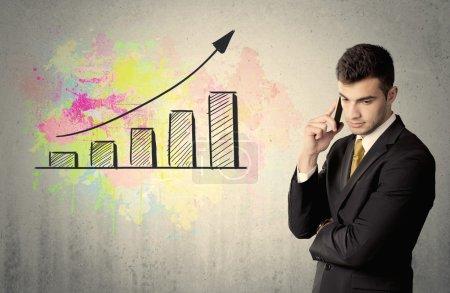 Photo pour Un homme d'affaires élégant debout devant un mur gris avec un concept de dessin graphique coloré en pleine croissance - image libre de droit