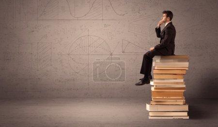 Photo pour Un homme d'affaires sérieux en costume assis sur un tas de livres géants devant un mur brun grisâtre avec des lignes dessinées, des angles, des nombres, des cercles et des courbes . - image libre de droit