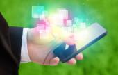 Ruka držící chytrý telefon s abstraktní zářící čtverce