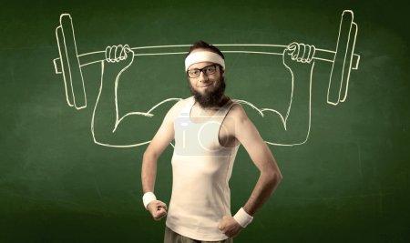 Photo pour Un jeune homme avec barbe et lunettes posant devant fond vert, imaginant comment il soulèverait du poids avec de gros muscles, illustré par le concept de dessin blanc . - image libre de droit