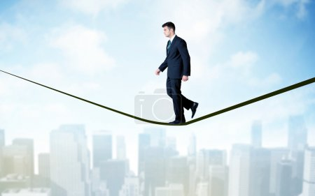 Salesman walking on rope above the city