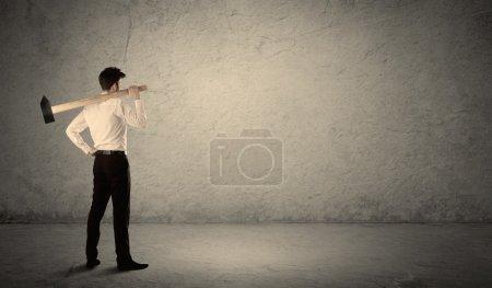 Photo pour Homme d'affaires debout devant un mur de fond grungy avec un marteau - image libre de droit