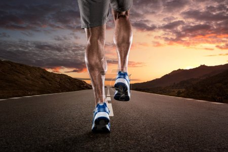 Photo for Close up of athlete's legs running on the empty road at the sunset - Royalty Free Image