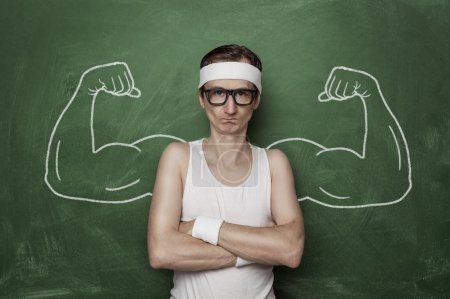 Photo for Funny sport nerd with fake muscles drawn on the chalkboard - Royalty Free Image