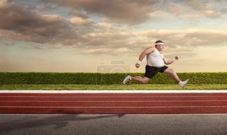 Funny overweight man speeding on the running track with copy spa