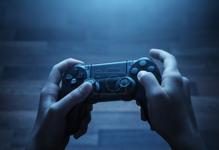 Photo for Close up of child hands playing the video game late at night - Royalty Free Image