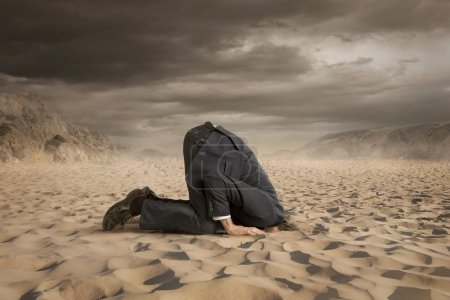 Photo for Young businessman hiding head in the sand - Royalty Free Image