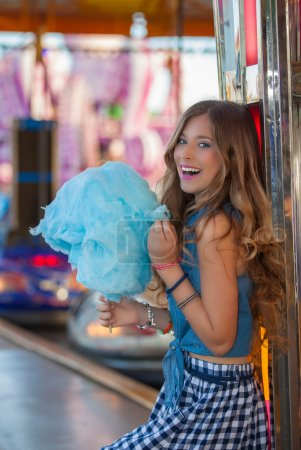 teen at fair eating candy floss or cotton.