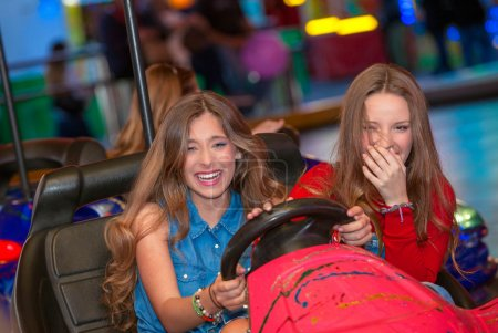 Foto de Teens at fun fair riding dodgems or bumper cars. - Imagen libre de derechos