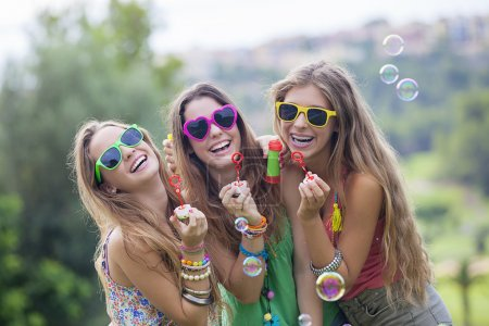 Photo for Happy smiling gropu of teen girls blowing bubbles - Royalty Free Image