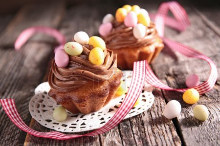 Photo for Chocolate Easter cupcakes with candies on table - Royalty Free Image